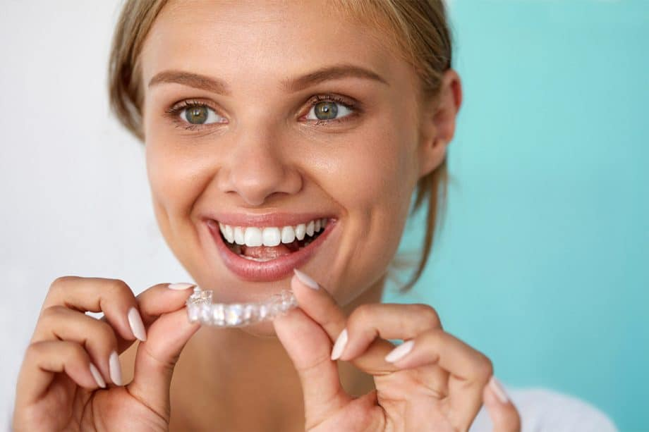 smiling woman holding Invisalign appliance